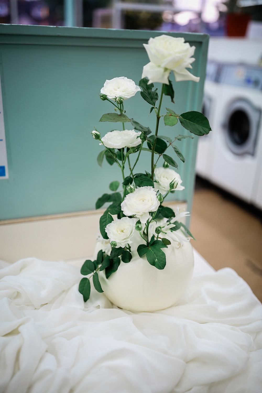Wedding cake that looks like a white ceramic flower pot, holding long stemmed white roses