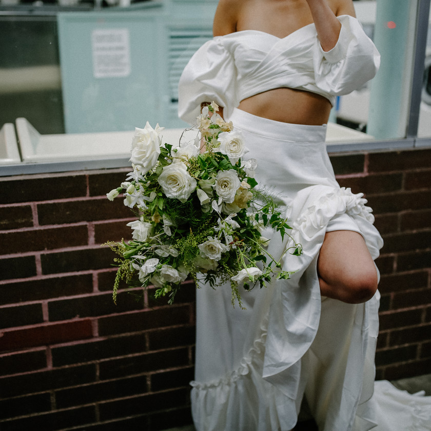 Bride standing outside laundromat, back against the brick holding her floral bouquet