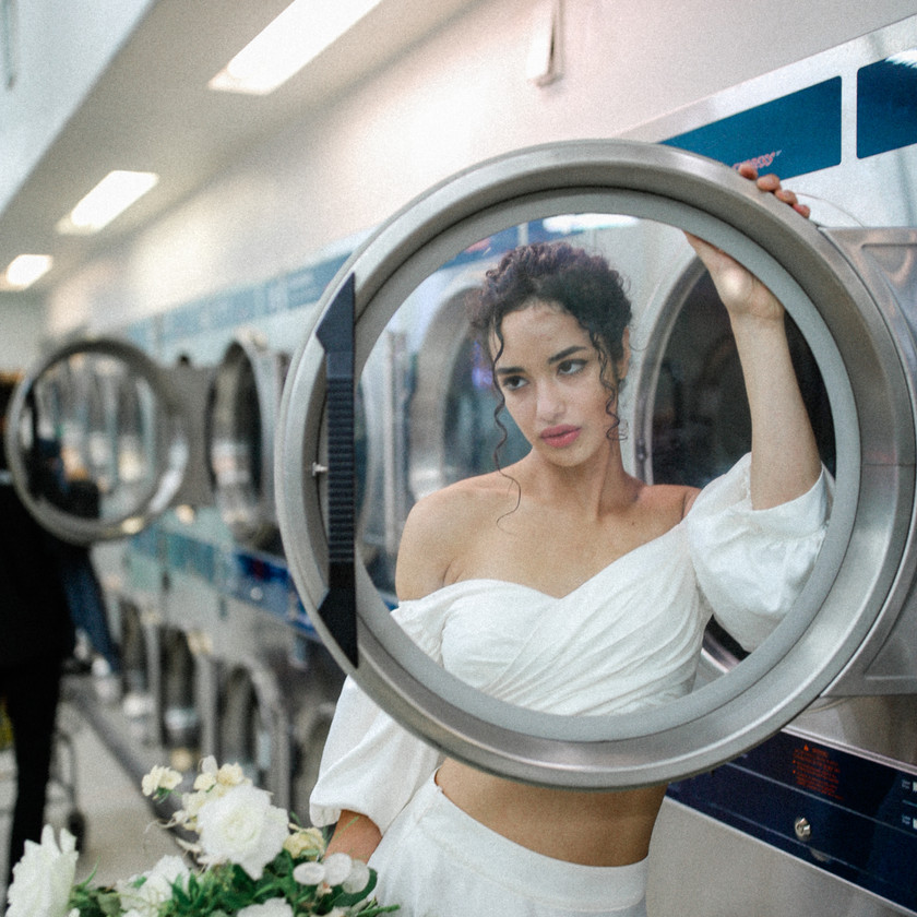 Bride at a laundromat looking through the door of the washing machine in her white off shoulder wedding dress