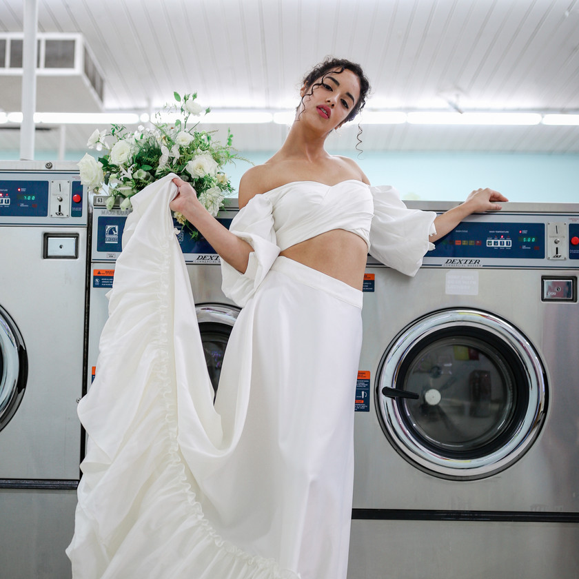 Bride holding her long train wedding gown staring at the camera and leaning on a washing machine
