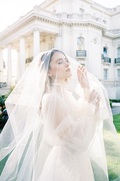 bride wearing affordable wedding dress with veil over her head in front of column mansion