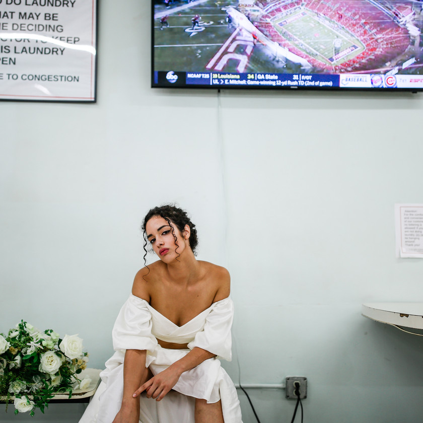 Girl seated in wedding dress with television behind her and table next to her in a laundromat