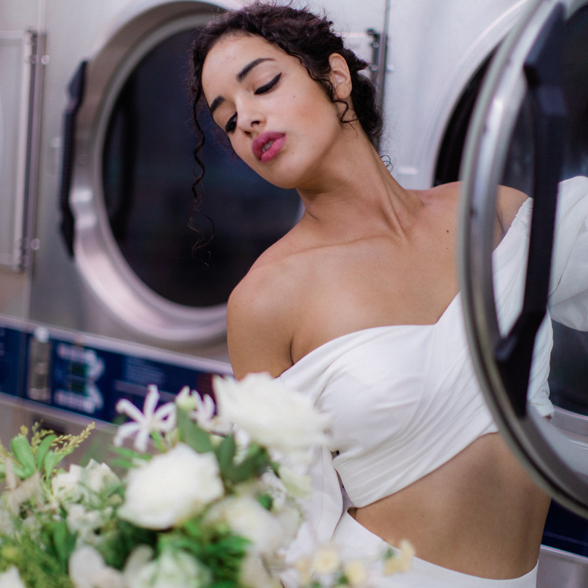 Bride holding flowers leaning back against a washing machine in two piece wedding dress