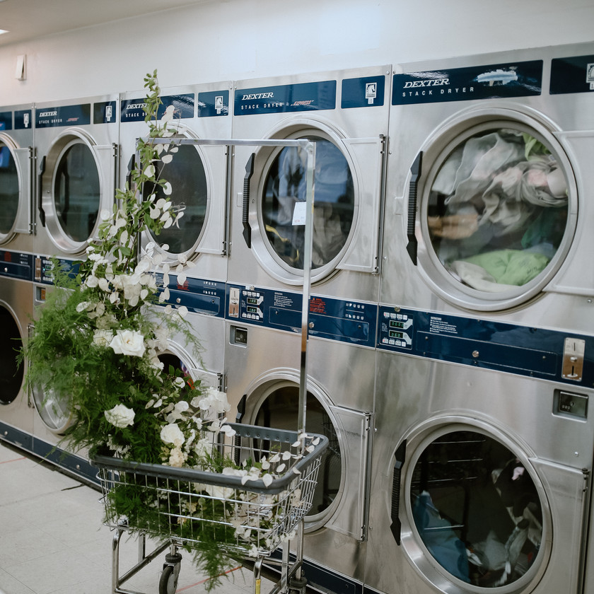 Detail shot of washing machines with wedding florals decorating the area on a laundry cart