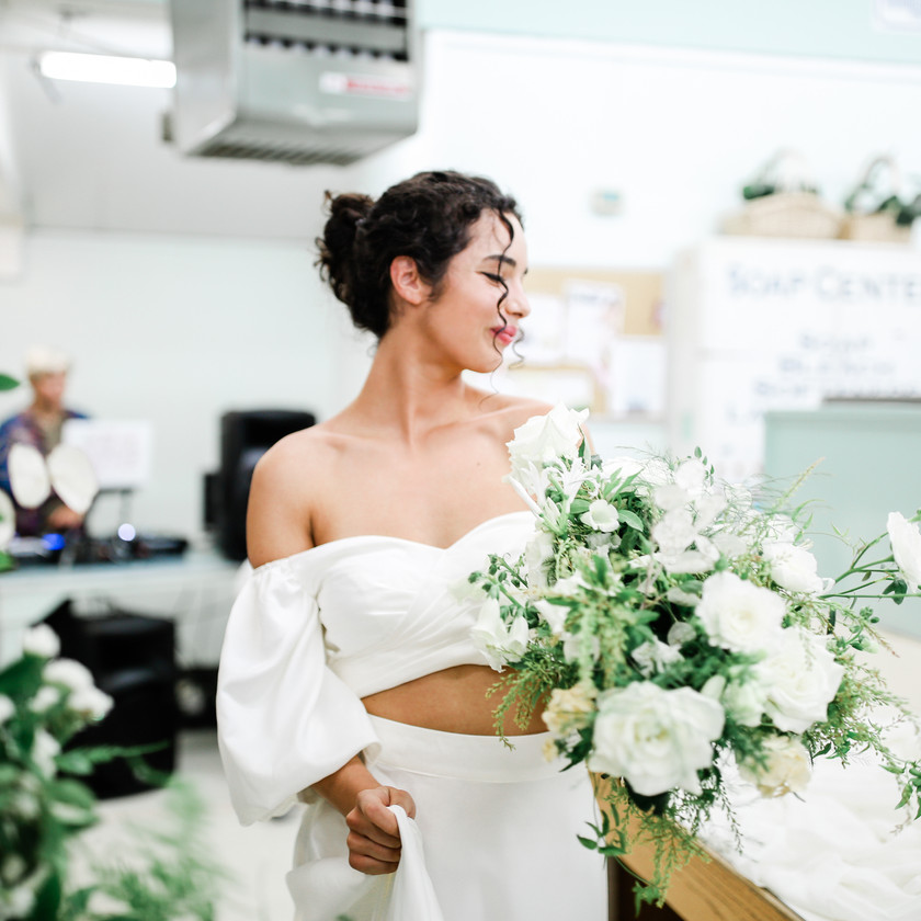 Bride smiling holding wedding bouquet at a laundromat wearing a two piece satin off shoulder wedding dress