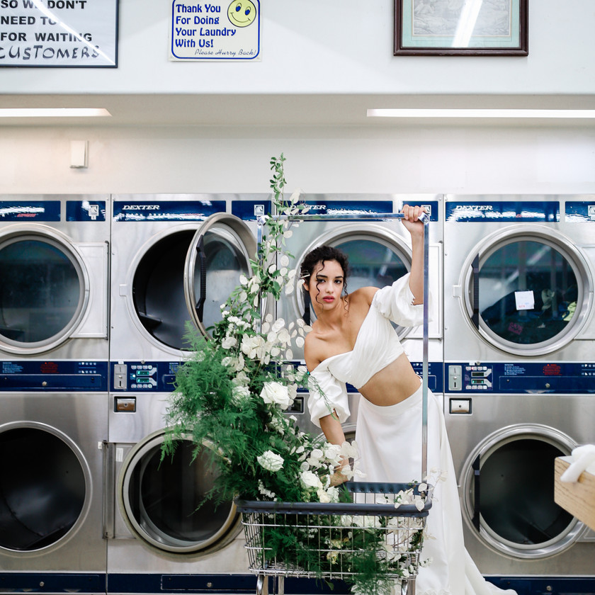 Bride leaning on a laundry cart at a laundromat with wedding florals on the cart wearing a two piece wedding dress