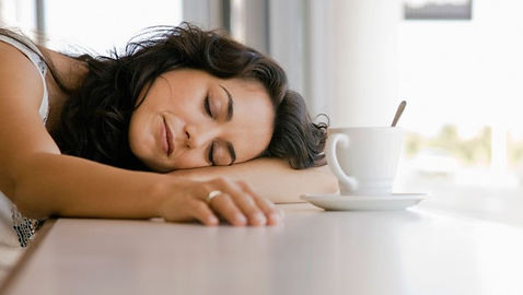 Woman sleeping with cup of coffee