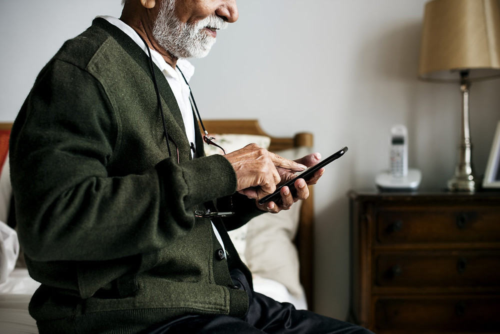 An elder man uses his cell phone to call a friend.