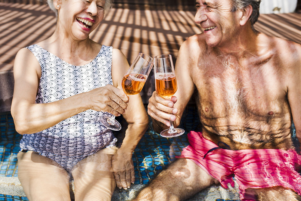 70+ couple enjoying a relaxing dip in the pool with a glass of wine.