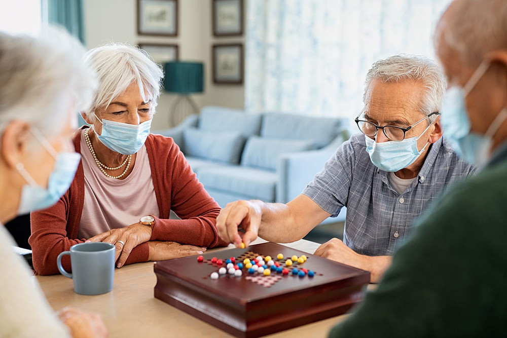 Elder friends playing board games indoors wearing face masks during covid-19.