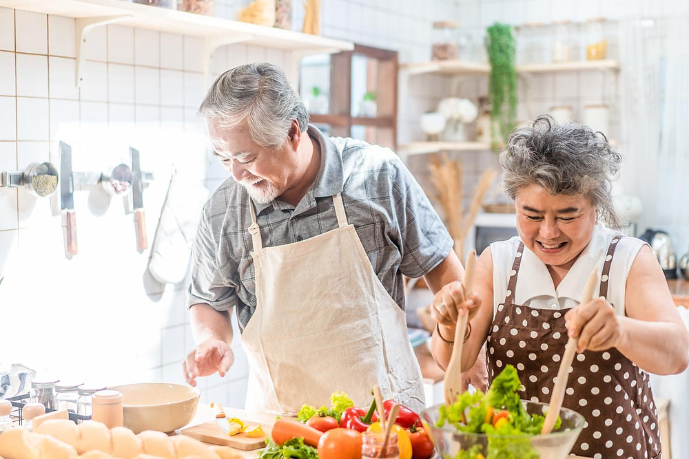 An elder couple enjoying themselves while cooking together.
