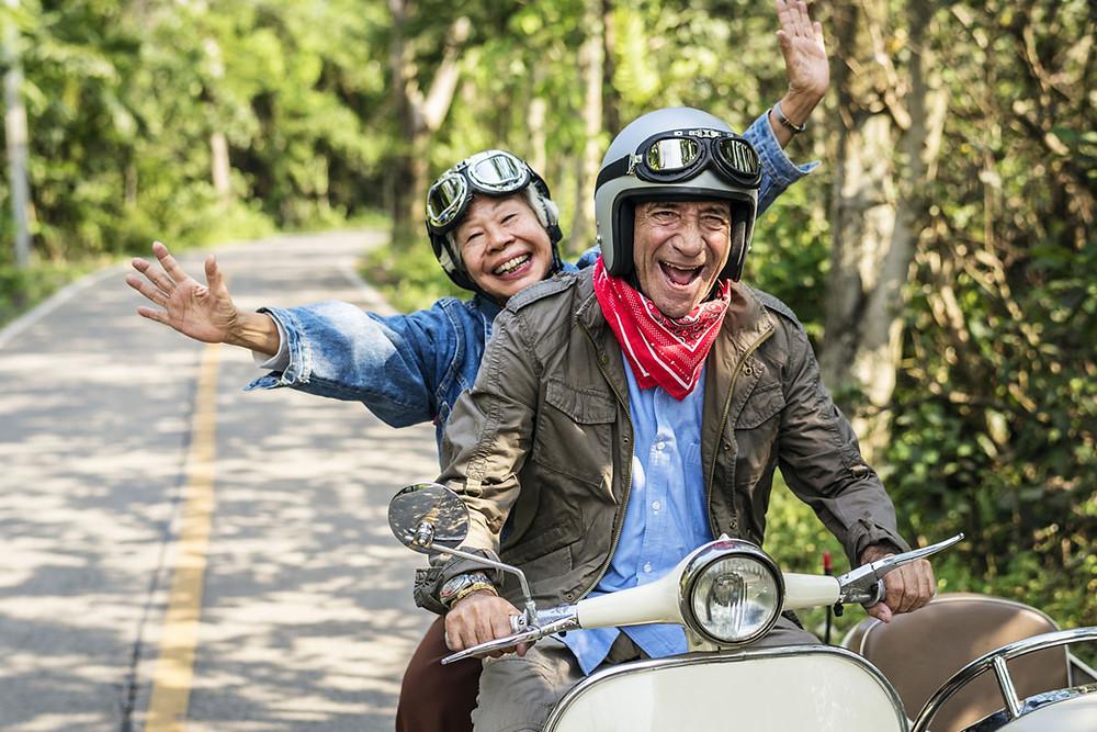 Elder couple enjoying a country ride on a vespa.