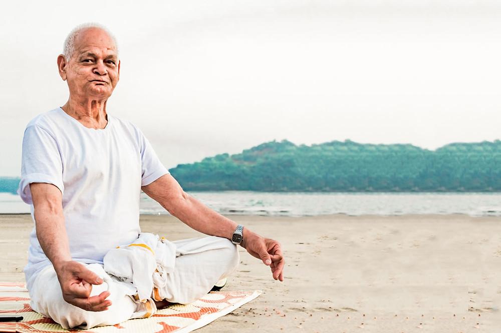 Elder man meditating on a beach.