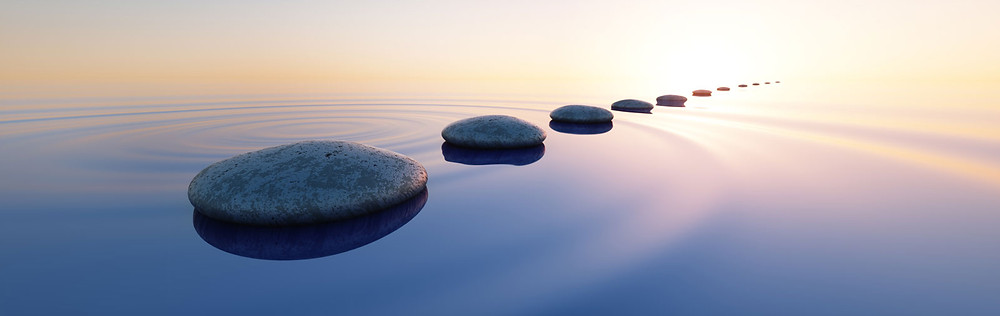 Stones set as a path through water with bright light reflecting off the water.