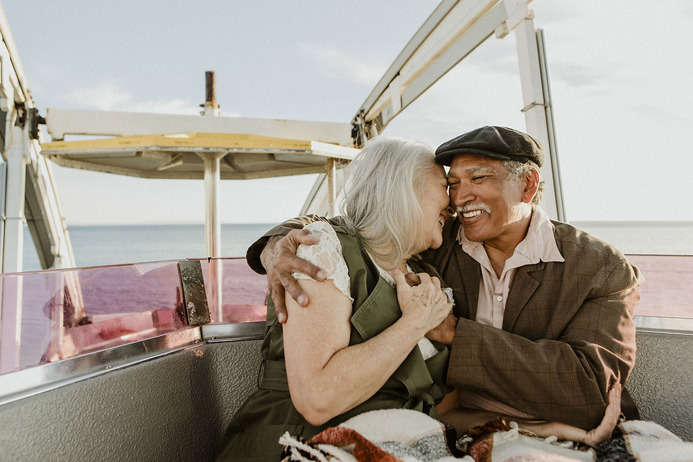 70+ couple smiling and embracing while enjoying time on a boat.