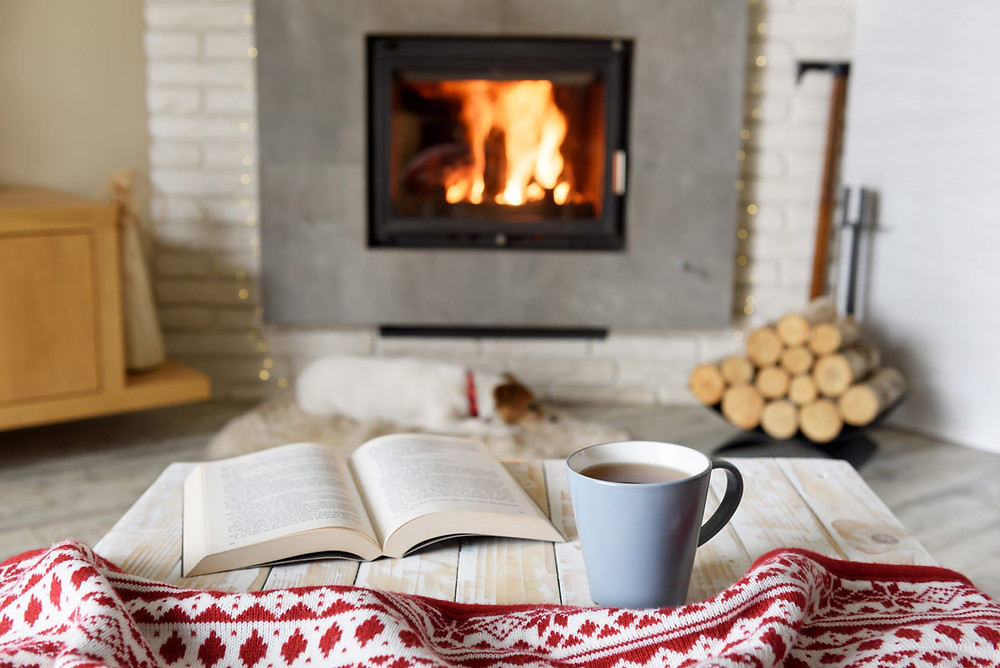 Creating a cozy space to get through the winter - a book and cocoa in front of a fire.