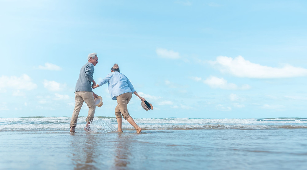 70+ couple playing on a beach in the waves while holding hands.