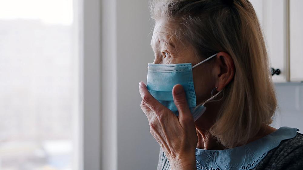 Elder woman wearing face mask indoors, feeling vulnerable.