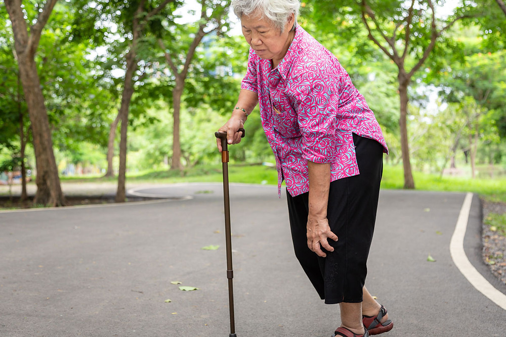 Elder woman with achy joints walking with a cane.