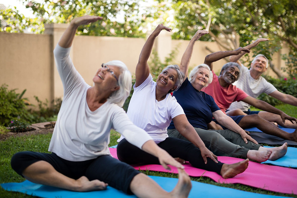 Active-elders-outside-doing-yoga-together-and-aging-well.