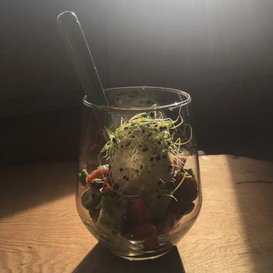 Wachsweiches Ei auf Avocado-Tomatensalat mit Koreander und Zwiebelsprossen