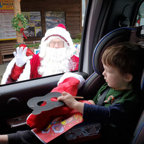 Santa greeting a child in the drive-through