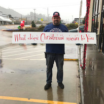 Justin Bales displaying the sign he donated for the Children's Youth Art Competition