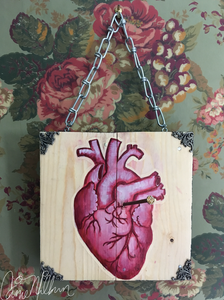 anatomical heart painted on wood with a nail into the heart