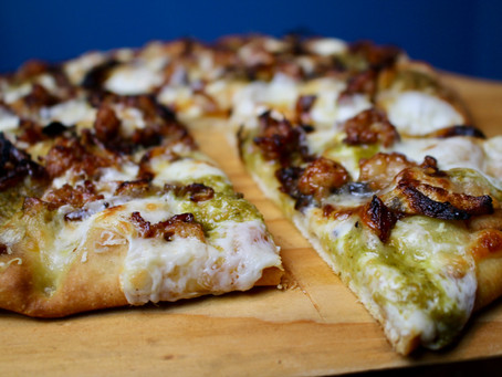 Pizza topped with Fresh Mozz, Pesto, Caramelized Onions & Spicy Sausage