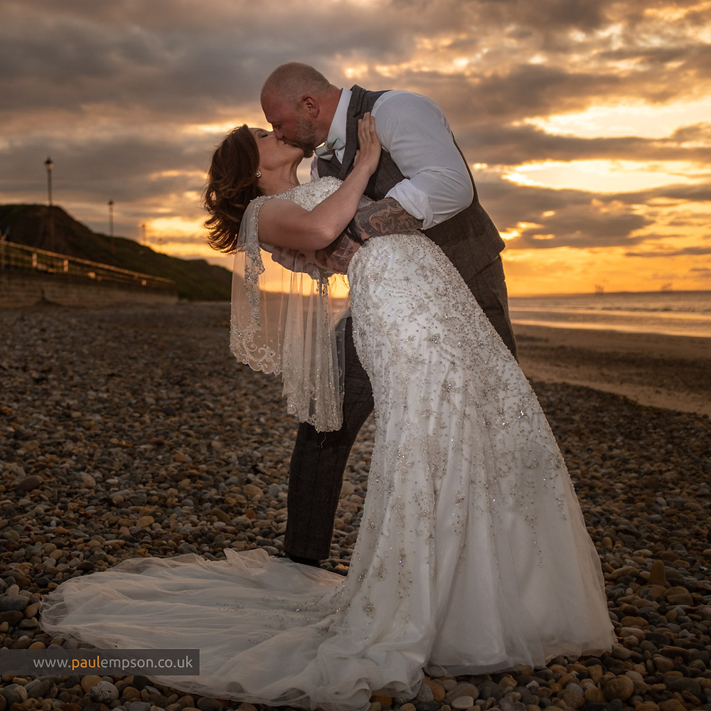 Bride & groom kiss bathed in golden sunset at Saltburn beach