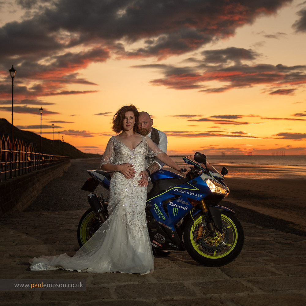 Bride & groom on motorbike with golden sunset  on Saltburn beach