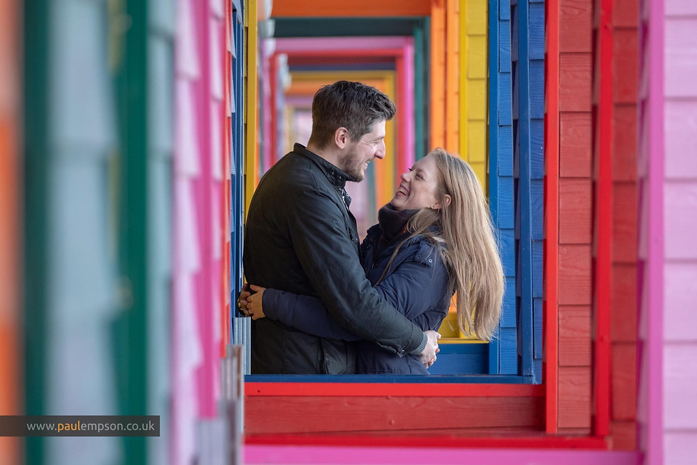 smiling & laughing couple at the colourful beach huts at Saltburn beach