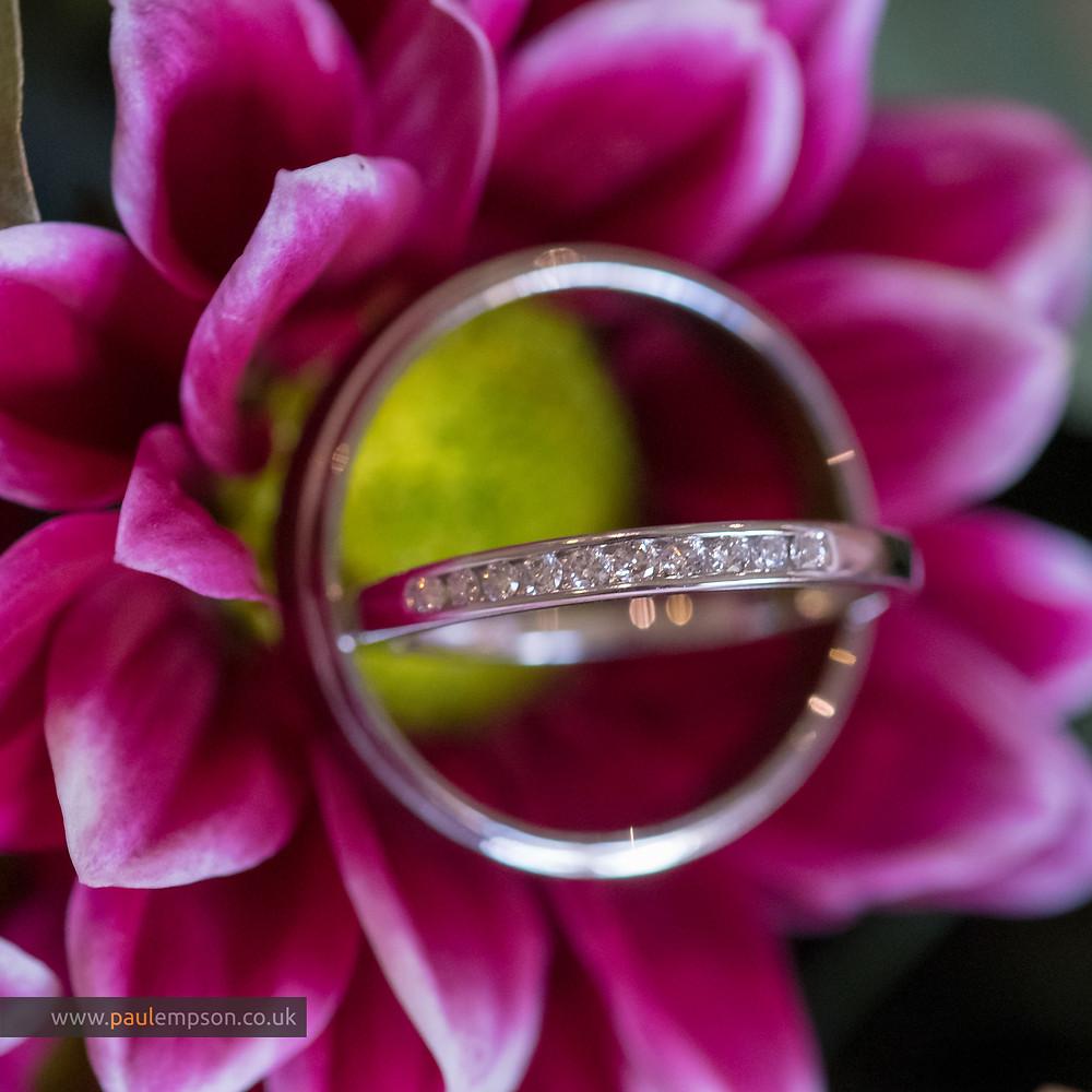detail of wedding rings balanced in wedding flowers