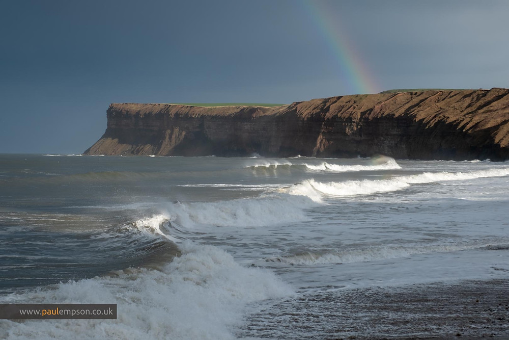 Rainbow over Huntcliffe at Saltburn as big waves roll in