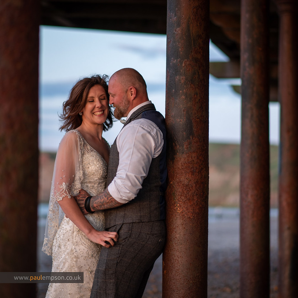 Laughing bride against her groom under Saltburn Pier at sunset