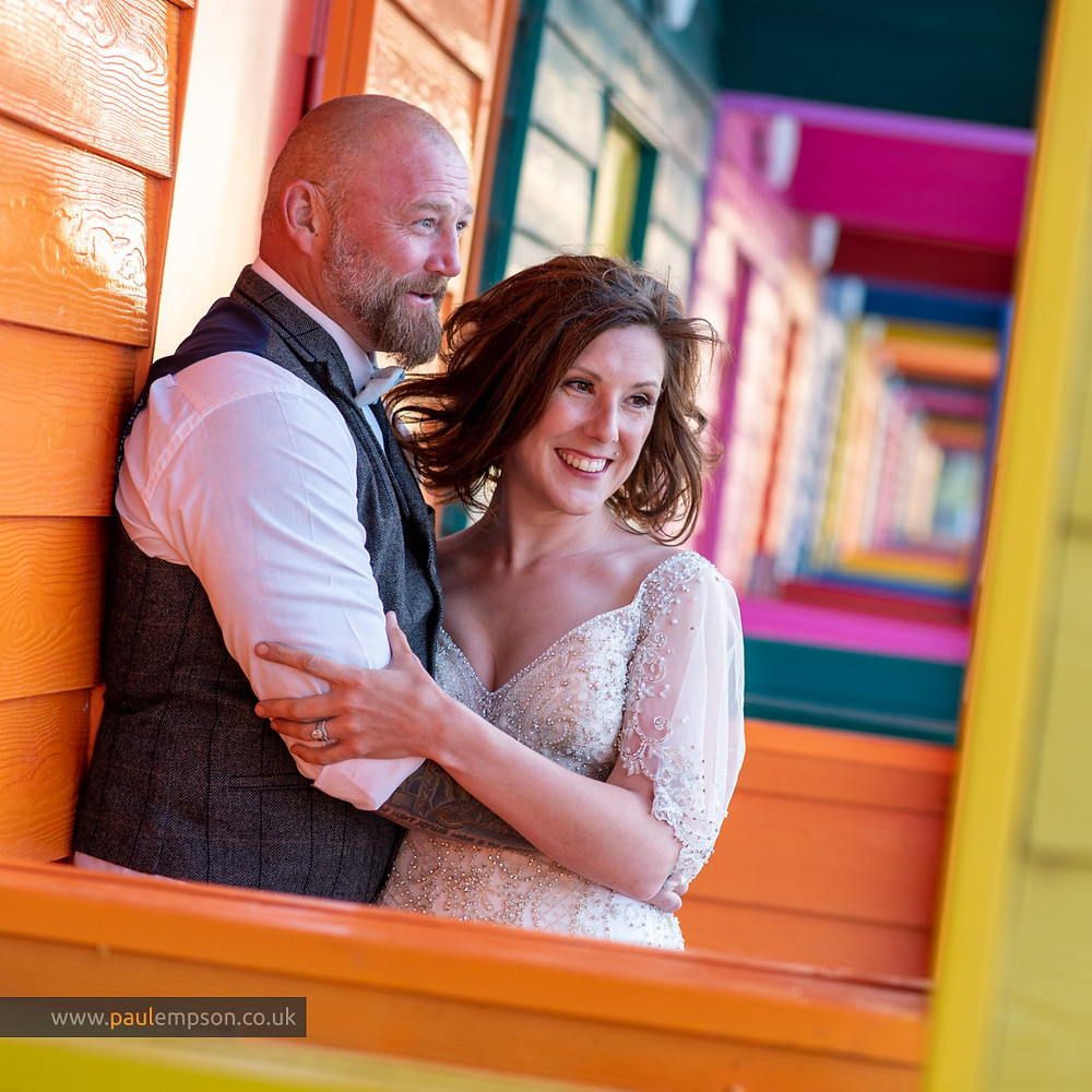 bride & groom in the colourful beach huts at Saltburn beach