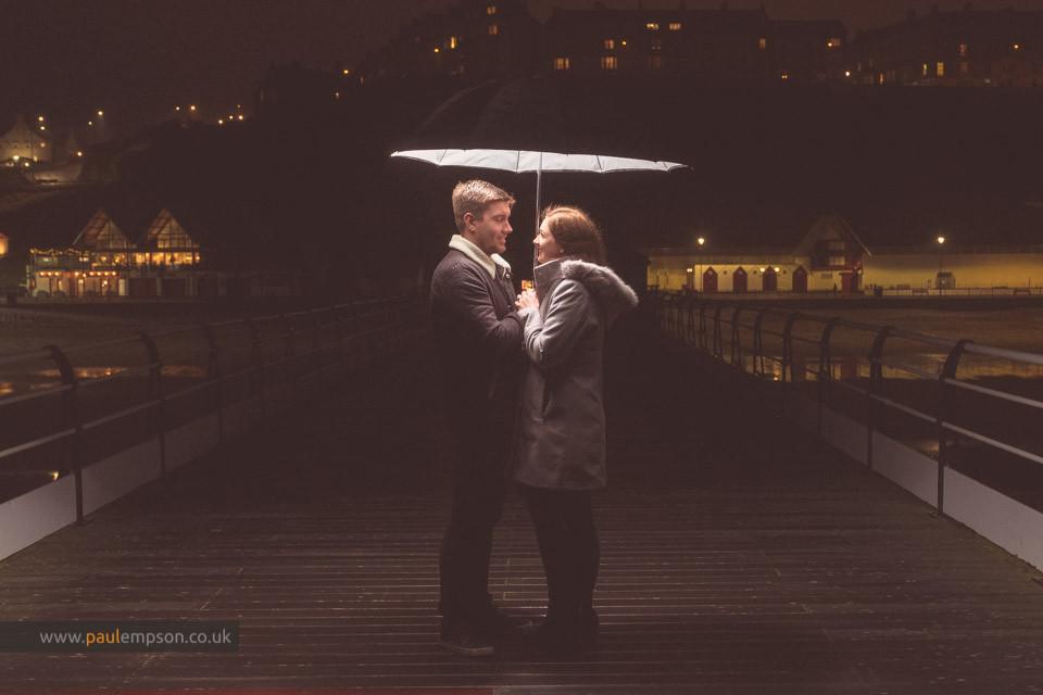 night time shot of couple on Saltburn Pier under an umbrella
