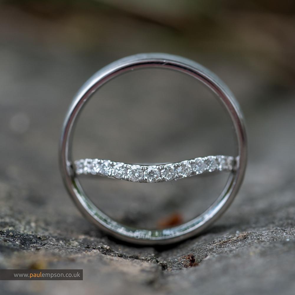 wedding rings balanced together on a stone church wall