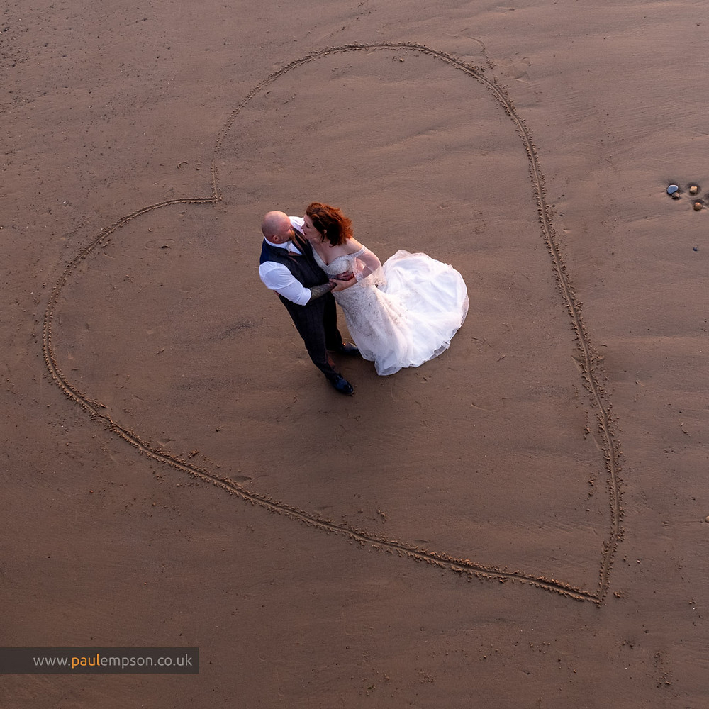 Bride & groom together on Saltburn beach in a sand drawn love heart