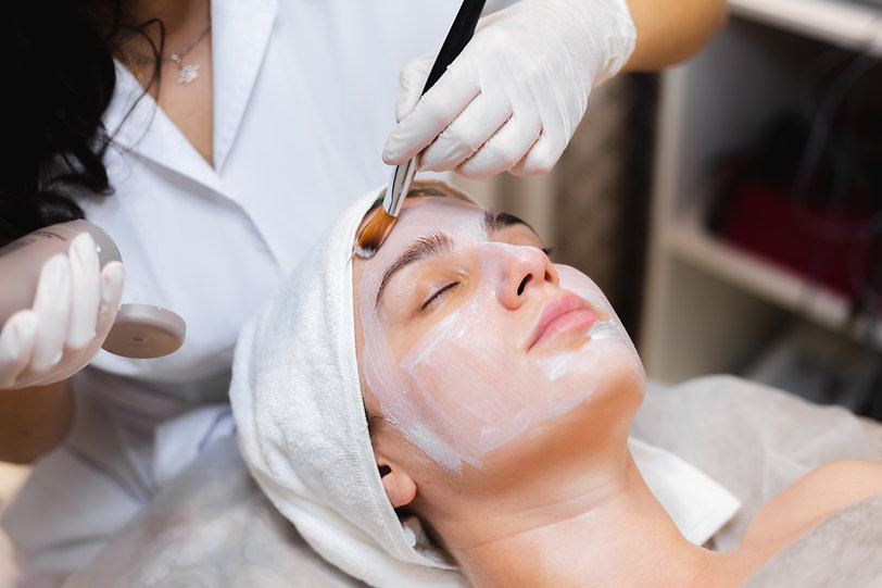 beautician-with-brush-applies-white-moisturizing-mask-to-the-face-of-young-girl-client-in-