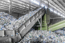 escalator with a pile of plastic bottles at the factory for processing and recycling.jpg