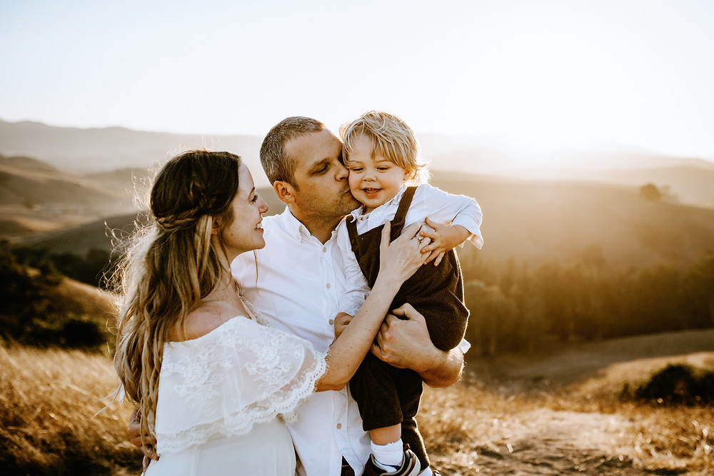 family of three snuggling together, dad holding toddler boy while mom reaches for him, maternity photo session Sonoma County, golden hour