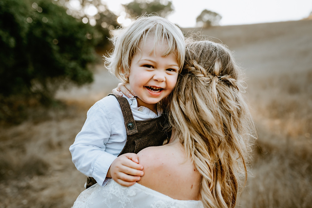 smiling toddler boy looking at camera while his pregnant mother is holding him up