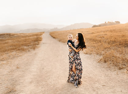gorgeous mother holding her toddler son with the sun setting behind them, in the middle of a trail, lifestyle family photographer for sonoma, marin and napa county, diana jex