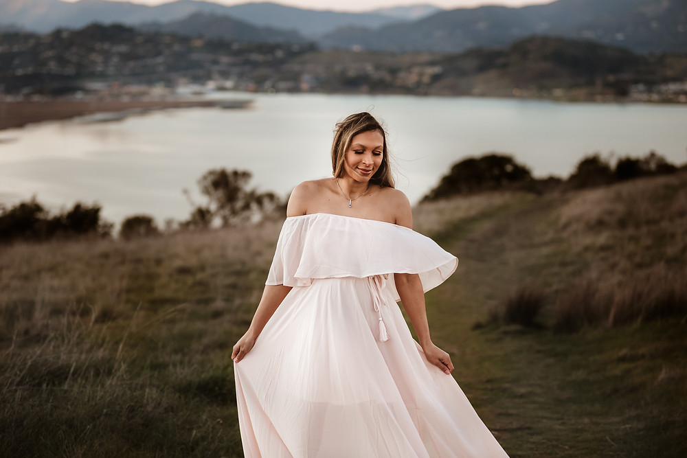expecting mother holding and twirling in long light pink maxi maternity dress, sunset and San Francisco Bay behind her, petaluma family photography, marin family photographer