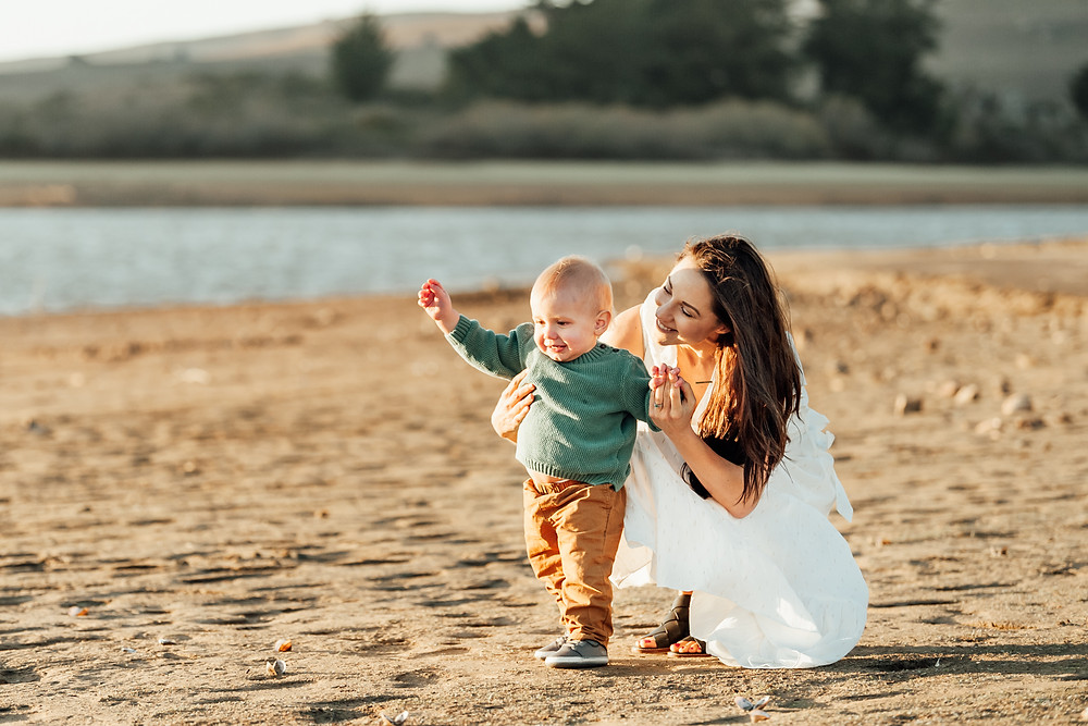 mom holding toddler son while he is learning to walk, baby boy in green sweater and brown pants, water in background, dirt landscape, sunset Sonoma County family photographer, Petaluma family photographer Diana jex