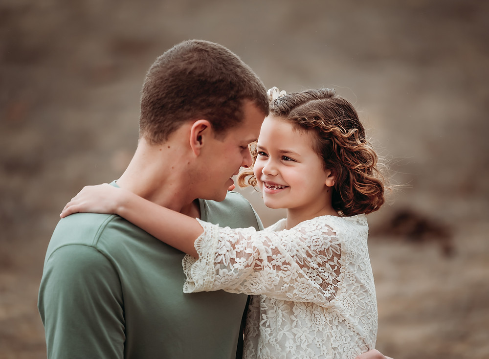 daughter being held by her dad, smiling and looking at him, arms around his neck, dad sitting down holding his daughter, girl in lace white dress, dad in green shirt smiling, Sonoma County family photographer, Diana Jex