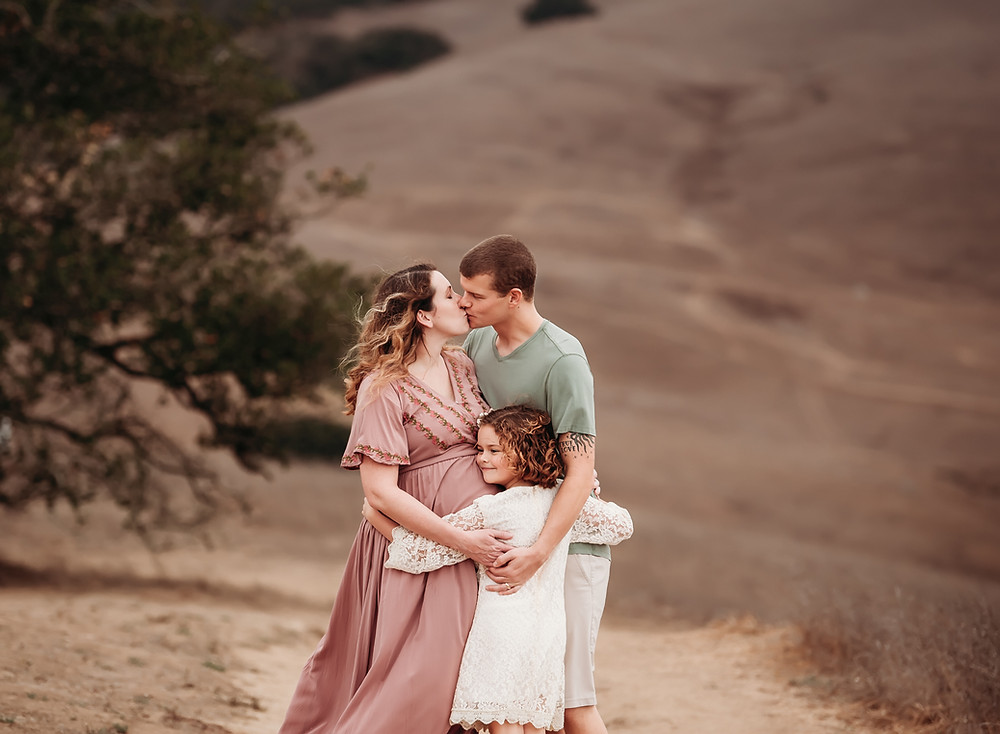 Family of three hugging each other at the top of a mountain in Sonoma County, grass is brown, mom in long blush pink maternity dress, dad in green shirt, little girl in white dress with lace, hugging mom's pregnant belly