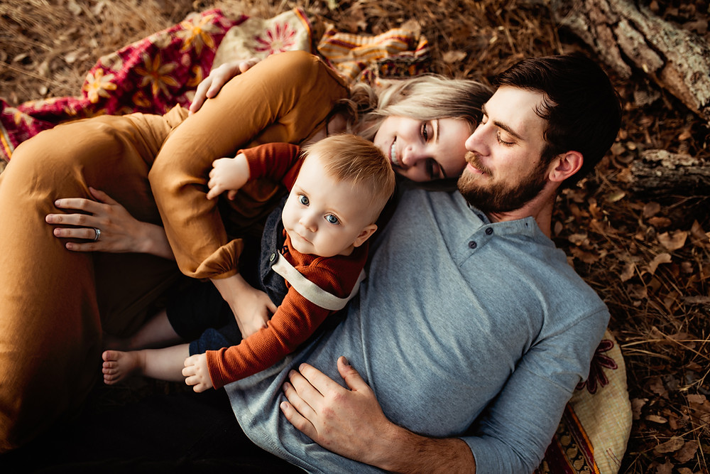 Family of three sitting laying down on blanket, photographed during golden hour, toddler son looking up at camera