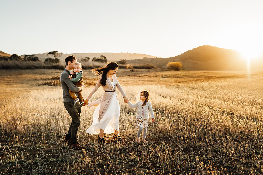 family of four holding hands and walking together towards sunset, daughter in white cardigan and dress looking back at mom, dad holding baby toddler boy, golden hour, sunset, Novato, Marin, Northern California, family photographer Diana Jex